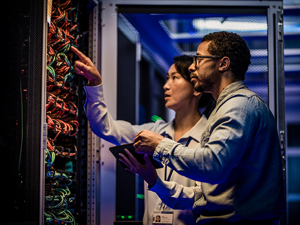 Male and female IT engineers checking servers in server room with help of tablet.