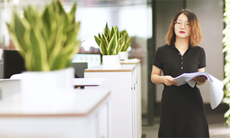 Smart businesswoman standing in modern office and holding papers